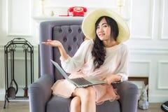 Красивая молодая азиатская женщина дома сидя на роскошном usi софы Стоковые Изображения RF
