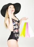 Красивая молодая дама в купальном костюме, большая черная шляпа на высоких пятках, держа красочные сумки и говоря на телефоне Стоковое Изображение RF