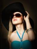 Красивая молодая дама в купальном костюме, большой черной шляпе на высоких пятках, и солнечных очках Стоковое фото RF