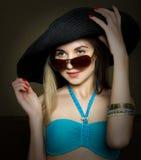 Красивая молодая дама в купальном костюме, большой черной шляпе на высоких пятках, и солнечных очках Стоковая Фотография