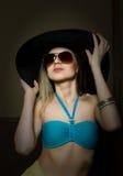 Красивая молодая дама в купальном костюме, большой черной шляпе на высоких пятках, и солнечных очках Стоковые Изображения RF