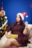 Красивая молодая дама в шляпе Санты около украшенный Стоковые Фото