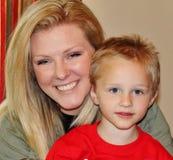 Красивая молодая дама держа милый усмехаться мальчика Стоковая Фотография