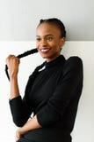 Красивая молодая африканская женщина касаясь ее длинным волосам на предпосылке студии стоковые фотографии rf