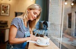 Красивая молодая беременная девушка сидя в кассете a чтения кафа Стоковое Фото