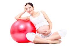 Красивая молодая беременная женщина сидя с fitball стоковое изображение rf