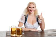 Красивая молодая белокурая девушка выпивает из oktoberfest глиняной кружки пива Стоковая Фотография