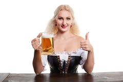 Красивая молодая белокурая девушка в традиционном костюме выпивает из oktoberfest глиняной кружки пива Стоковые Фотографии RF