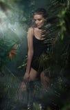 Красивая молодая белокурая девушка представляя в тропическом лесе стоковые фотографии rf
