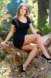 Красивая молодая белокурая женщина в платье коктеиля сидит на Стоковое фото RF