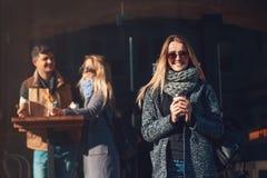 Красивая молодая белокурая женщина в солнечных очках держа кофейную чашку и круассан и смотря камеру с улыбкой стоковая фотография rf