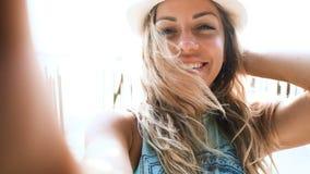 Красивая молодая белокурая женщина в шляпе принимая selfie на пляже на дуть захода солнца видеоматериал