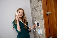 Красивая молодая белокурая женщина говоря на внутренной связи Стоковое Фото