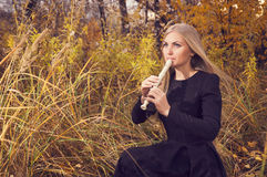 Красивая молодая белокурая женщина играя рекордера каннелюры в лесе осени Стоковое Изображение