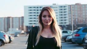 Красивая молодая белокурая женщина идя вниз с автостоянки в ярком солнечном свете, взглядов к камере и улыбок seductively горяче сток-видео