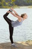 Красивая молодая белокурая женщина при атлетическое тело делая протягивающ тренировку outdoors Стоковые Фотографии RF