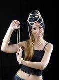 Красивая молодая белокурая женщина с длинними волосами и жемчугом танцует востоковедный таец на темной предпосылке Стоковое Фото