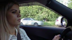 Красивая молодая белокурая женщина управляет видео отснятого видеоматериала запаса автомобиля видеоматериал