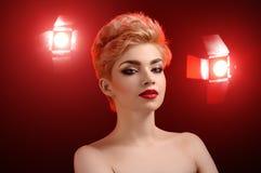 Красивая молодая белокурая красная lipped женщина представляя в художническом красном цвете l Стоковые Изображения RF