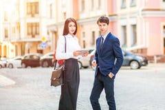 Красивая молодая бизнес-леди и красивый бизнесмен в официально костюмах используют цифровую таблетку в предпосылке города Стоковые Изображения