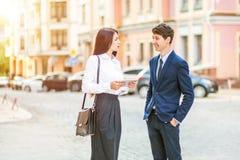 Красивая молодая бизнес-леди и красивый бизнесмен в официально костюмах используют цифровую таблетку в предпосылке города Стоковая Фотография