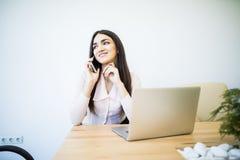 Красивая молодая бизнес-леди сидя на столе офиса и говоря на сотовом телефоне Стоковая Фотография RF