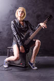 Красивая молодая блондинка одела в черной кожаной куртке с электрической гитарой на черной предпосылке Стоковое Изображение RF