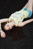 Красивая молодая девушка битника лежит в середине дороги асфальта, Стоковая Фотография RF