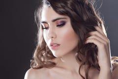 Красивая молодая девушка брюнет с длинными волнистыми волосами Курчавый стиль причёсок Смотреть вниз Стоковое Изображение