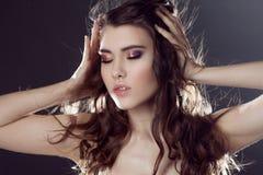 Красивая молодая девушка брюнет с длинными волнистыми волосами Курчавый стиль причёсок Черная предпосылка Стоковая Фотография