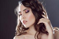 Красивая молодая девушка брюнет с длинными волнистыми волосами Курчавый стиль причёсок Серая предпосылка Стоковая Фотография RF