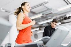 Красивая молодая женщина бежать на третбане в спортзале Стоковое Изображение
