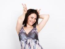 Красивая молодая женщина брюнет в красочном платье представляя и выражает различные эмоции выставки рук женщины различные Стоковая Фотография RF