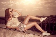 Красивая молодая женщина брюнет представляя над предпосылкой города захода солнца стоковая фотография