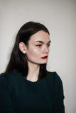 Красивая молодая женщина брюнет против белой стены Стоковые Фото
