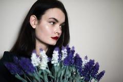 Красивая молодая женщина брюнет против белой стены Стоковое фото RF