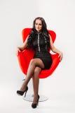 Красивая молодая женщина брюнет с длинными волосами в черном платье сидя на предпосылке белизны стула стоковое фото rf