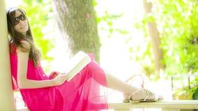 Красивая молодая женщина брюнет читая книгу акции видеоматериалы