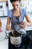 Красивая молодая женщина варя суп с овощами дома Стоковое Фото