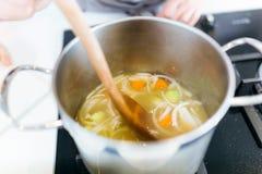 Красивая молодая женщина варя суп с овощами Стоковое фото RF