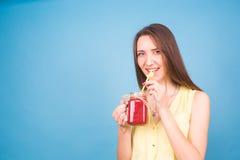 Красивая молодая женщина выпивает smoothie клубники на голубой предпосылке Здоровая органическая концепция пить Люди на диете Стоковое Фото