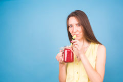 Красивая молодая женщина выпивает smoothie клубники на голубой предпосылке Здоровая органическая концепция пить Люди на диете Стоковые Изображения RF