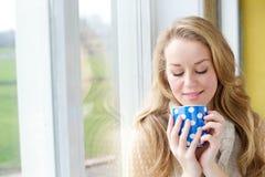 Красивая молодая женщина выпивая чашку чаю Стоковая Фотография RF