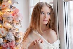 Красивая молодая женщина в белизне около рождественской елки Beautifu стоковые изображения