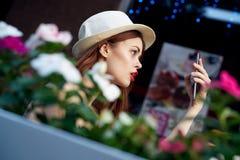 Красивая молодая женщина в белой шляпе делая selfie сидя в кафе на улице лета стоковые фотографии rf