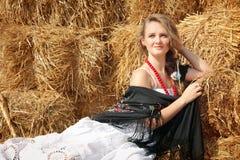 Красивая молодая женщина в белые sundress приближает к стогу сена Стоковая Фотография