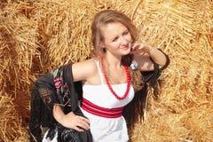 Красивая молодая женщина в белые sundress приближает к стогу сена Стоковое Изображение RF
