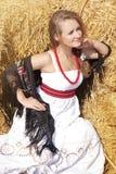 Красивая молодая женщина в белые sundress приближает к стогу сена Стоковое Фото