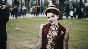 Красивая молодая женщина в винтажном флористическом платье и меховая шыба представляя на городе паркуют акции видеоматериалы