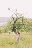 Красивая молодая женщина в длинном платье сирени с венком на голове стоя близко дерево Стоковое Фото
